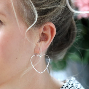 Lady wearing open heart drop earrings