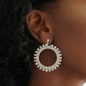 Girl wearing statement silver open circle hoop earrings with disc charms around the circumference.