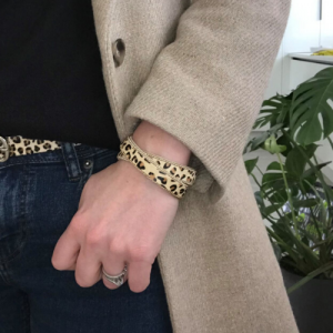 Lady wearing a cheetah print crossover animal print magnetic cuff bracelet. Genuine Leather Pony Hair Cuff Bracelet. Leopard Print Cuff.