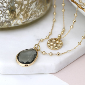 Worn gold double chain necklace with hammered disc & large grey crystal drop